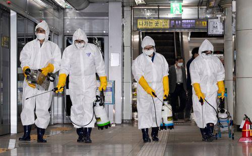 2月28日,在韩国首尔,工作人员在光化门地铁站进行消毒。新华社发(李相浩摄)
