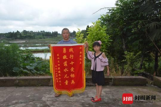 黄士荣和娜娜举着黄建生前获得的锦旗