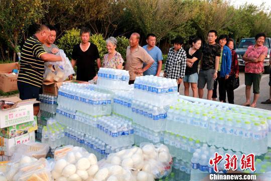 8月24日,志愿者在潍坊寿光市营里镇为灾民免费发放物资。 梁�摹∩�