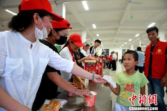 8月24日,志愿者在潍坊寿光市营里镇第二初级中学安置点为灾民发放救援物资。 梁�� 摄