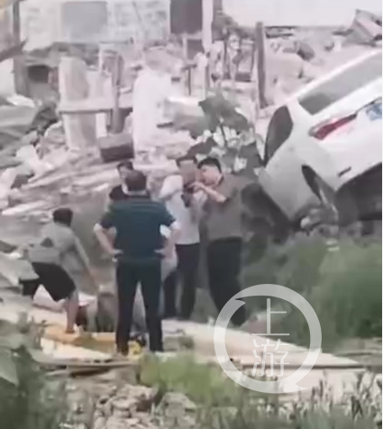 ▲王峥驾驶的白色轿车停在废墟上,胡华东倒在一旁。知情人士供图
