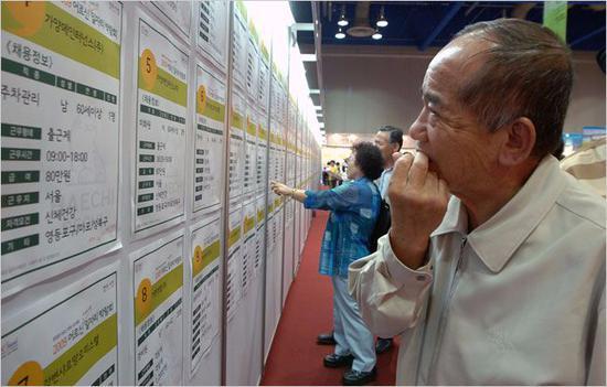 老人在招聘会上查看墙上的职位信息。Seokyong Lee/摄