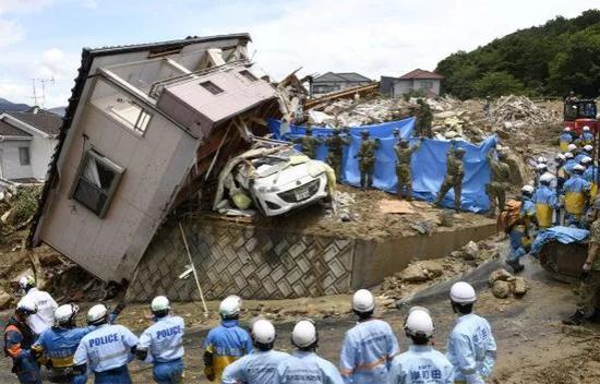 7月9日,在日本广岛,救援人员在被损毁的房屋废墟上搜救。新华社/路透