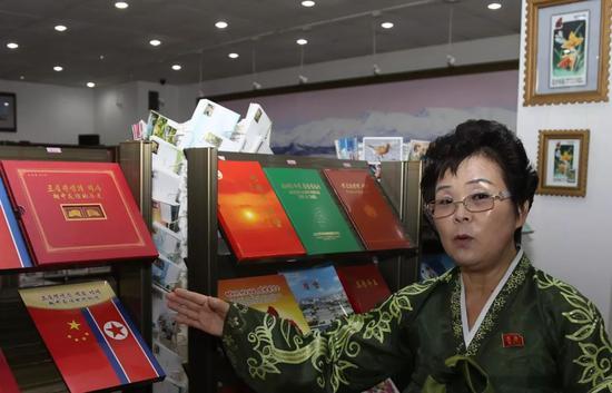 博物馆负责人金惠晶向记者介绍朝中友谊主题的邮票集。新华社记者程大雨摄。