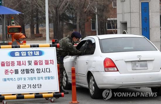 2月21日,在忠清南道鸡龙市鸡龙台空军气象团正门,工作人员正对出入人员进行检查。来源:韩联社