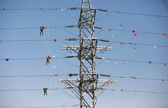 2020年1月16日,印度艾哈迈达巴德,电力公司工作人员清理缠绕在电线上的风筝线。