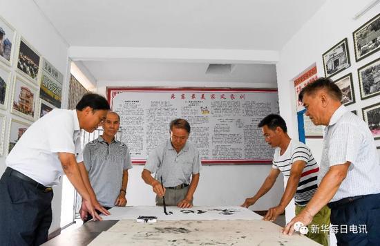 丹村村民退休教授王建光(中)在丹村艺术展厅内写毛笔字(5月8日摄)。