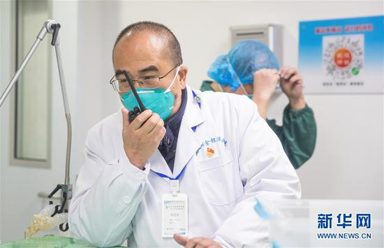 1月27日,在武汉金银潭医院综合病区楼,张定宇在接洽和谐事情。 新华社发(柯皓 摄)