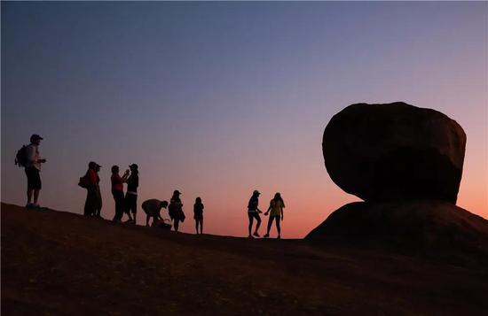 2015年11月9日,在哈拉雷东坡莎瓦山上,几名游客在一处平衡石景点旁边观赏日落。(新华社发,王新举摄)