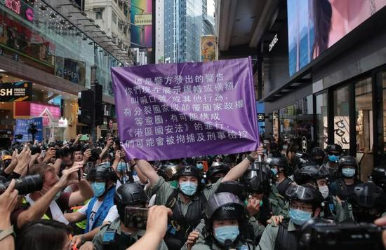 手持紫旗的 香港。警员(图源: 香港。01网站)