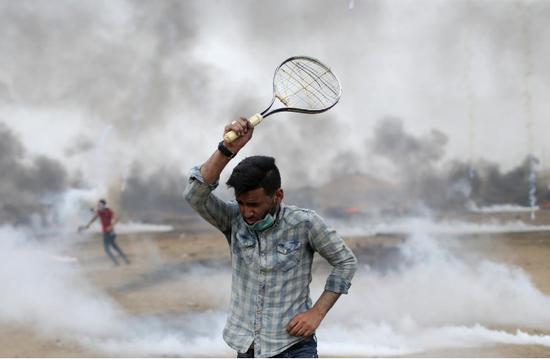 2018年5月4日,在加沙地带南部以色列-加沙边界处,巴勒斯坦人要求重返家园。在抗议活动中,示威者用球拍反击以色列军队发射的催泪弹。(图源:路透社)