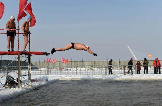 2018年1月23日,冬泳爱好者跃入哈尔滨松花江上的冬泳场。新华社记者王建威摄