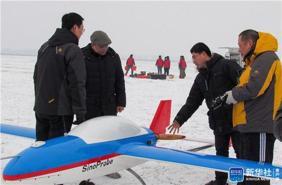 ↑著名地球物理学家黄大年(左二)及团队成员在极寒天气下进行固定翼无人机试飞(2013年1月20日摄)。新华社发