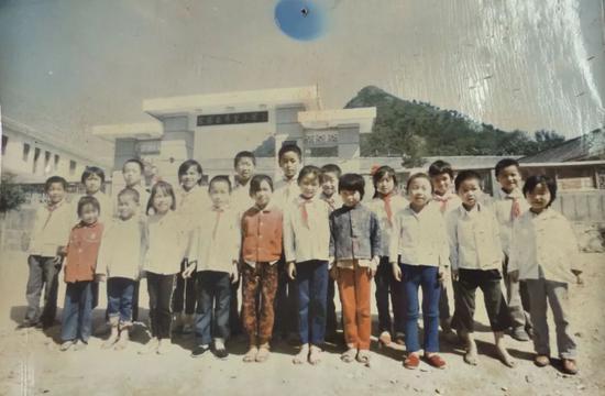 1990年第一批受到青少年发展基金会资助的学生在希望小学门前拍照留念。(翻拍金寨县希望小学资料图) 新京报记者 王飞 摄