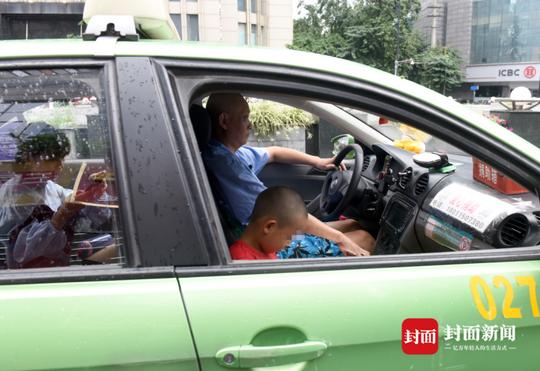 8月7日,成都红星路,出租车司机冯军带着儿子跑车。