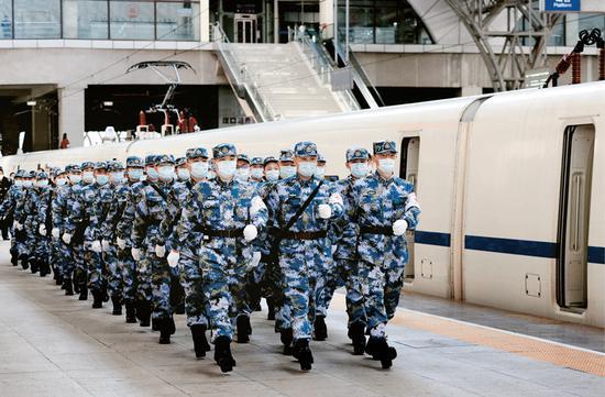 2020年2月17日,军队增派支援武汉抗击新冠肺炎疫情的又一批1200名医务人员,分别通过航空和铁路输送抵达武汉。图为医疗队员抵达武汉汉口火车站后军容严整地走出车站。 解放军报记者 王传顺/摄