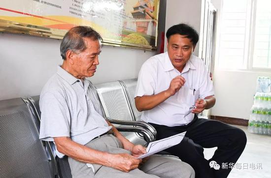 丹村村支书谢上强(右)在丹村便民服务站内与王建光交流(5月9日摄)。