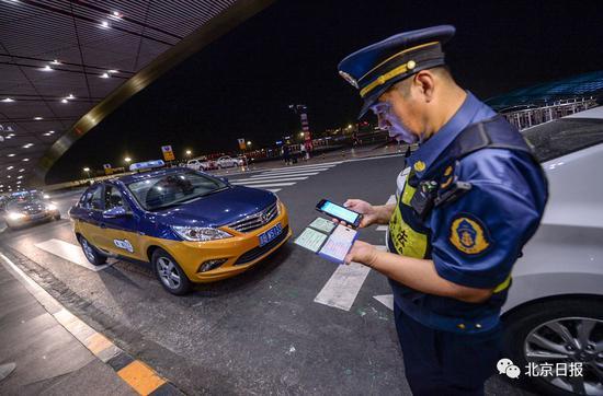 执法人员通过手持终端对出租车驾驶员信息进行核查。