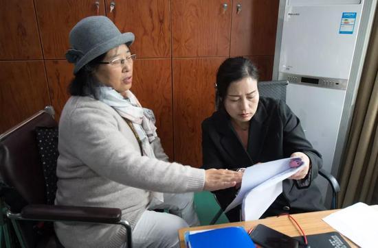 4月11日,吴素环(左)在中国盲文图书馆桐庐县支馆与工作人员讨论电影《可可西里》的解说稿。