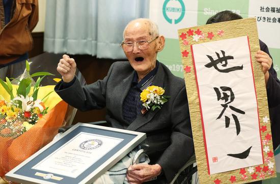 112岁的渡边和他的书法作品(朝日新闻)