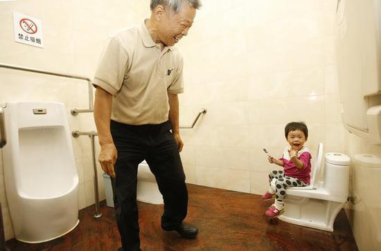 """在位于上海徐家汇公园内的""""第三卫生间"""",徐老伯带小孙女来体验小马桶 图片来源:新华社"""
