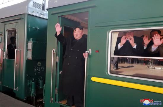 朝中社2月24日提供的照片显示,朝鲜最高领导人金正恩在专列上向平壤火车站内送行人员?#37038;?#33268;意。新华社/朝中社