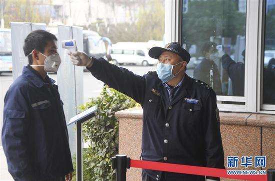 2月10日,工人在进入位于重庆市两江新区的长安福特变速器工厂前接受体温检测。新华社记者王全超摄
