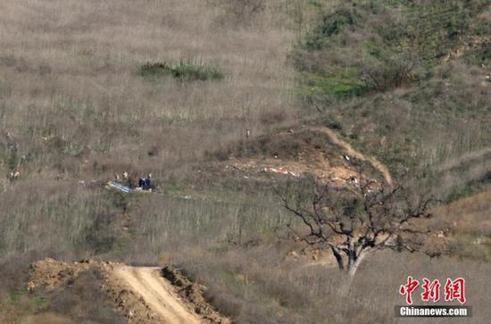 资料图:当地时间1月27日,调查人员在美国加州小城卡拉巴萨斯的山坡上,对直升机坠毁事故进行调查。26日,科比·布莱恩特的私人直升机在卡拉巴萨斯坠毁。中新社记者 刘关关 摄