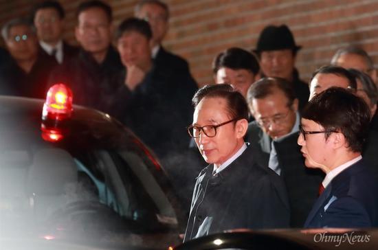 22日晚,李明博被押送至拘留所前,从家中走出