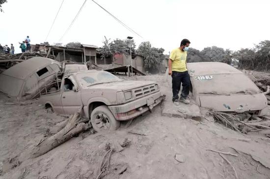 6月4日,在危地马拉埃斯昆特拉省圣米格尔洛斯卢特斯,一名男子走过被火山灰覆盖的汽车。新华社发