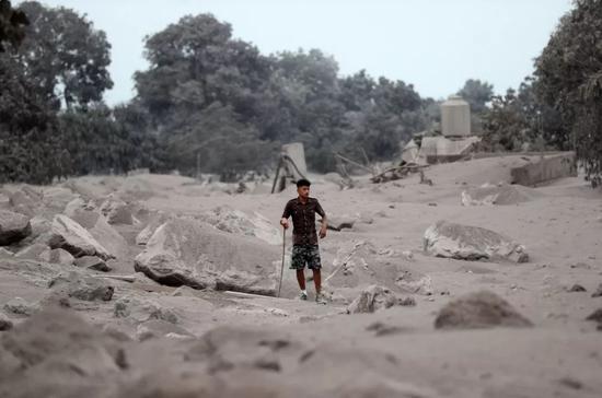 6月4日,在危地马拉埃斯昆特拉省圣米格尔洛斯卢特斯,一名男子站在被火山灰覆盖的村子里。新华社发