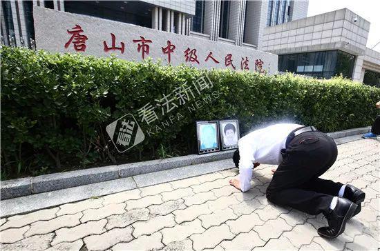 廖海军给父母遗像下跪。摄/记者 杨小嘉