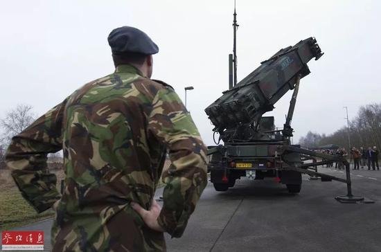 """▲资料图片:在荷兰德佩尔空军基地,一名军人望着向媒体展出的""""爱国者""""反导系统。新华社/路透"""