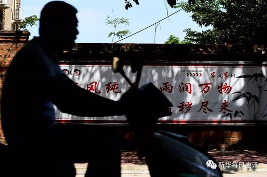 丹村村民骑车经过写着家风家训的标语墙(5月9日摄)。