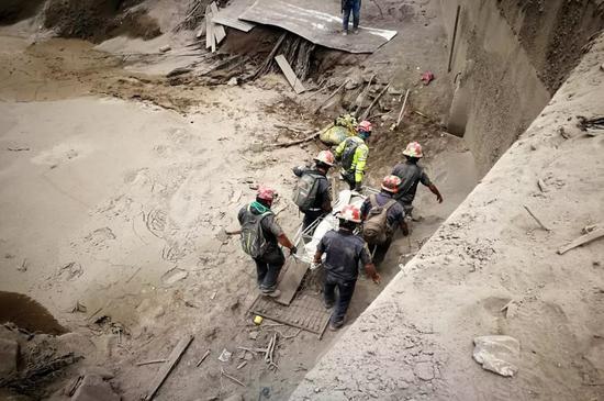 6月4日,在危地马拉埃斯昆特拉省圣米格尔洛斯卢特斯,救援人员在富埃戈火山喷发后展开工作。新华社发
