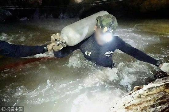 一名參與救援的前泰國海軍特種部隊成員6日在執行運送氧氣瓶的任務。圖片來自視覺中國