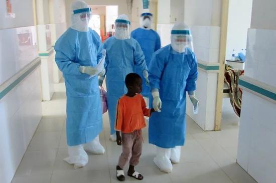 2014年10月11日,在塞拉利昂首都弗里敦,来自中国的医护人员护送留观患者进入病房。由中国北京302医院30名医生护士组成的解放军援塞医疗队在一个月前抵达弗里敦参与抗击埃博拉疫情。新华社发(孙捷摄)