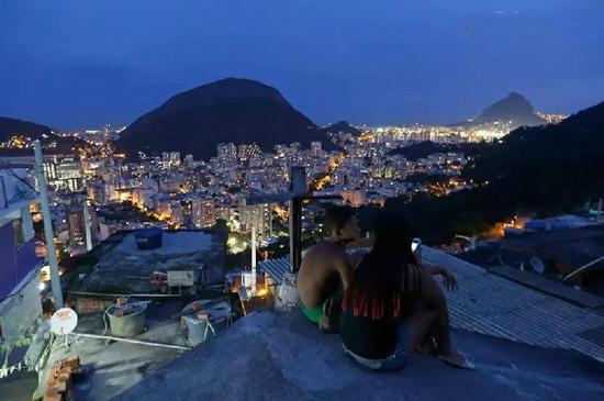 男孩和女孩坐在贫民窟的屋顶,不远处是高档街区