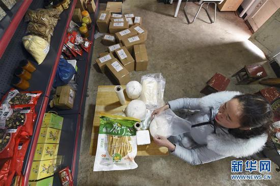 """2月19日,在位于甘肃省陇南市徽县水阳镇石滩村的家中,梁倩娟为买家打包货物。她开办""""陇上庄园""""网店,将当地出产的农产品通过网络销售,带动了乡亲们脱贫增收。新华社记者 范培珅 摄"""