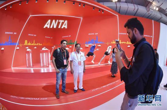 在一年一度的中国(晋江)国际鞋业暨国际体育产业博览会上,来自印度的客商在安踏展位前留影(2018年4月19日摄)。新华社记者 宋为伟 摄