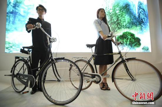 """模特展示复刻版的新中国第一辆国产""""飞鸽1950""""自行车(左一),它的旁边,则是1989年作为""""国礼""""送给时任美国总统老布什访华礼物的复刻车(右一)。 图片来源:中新网"""