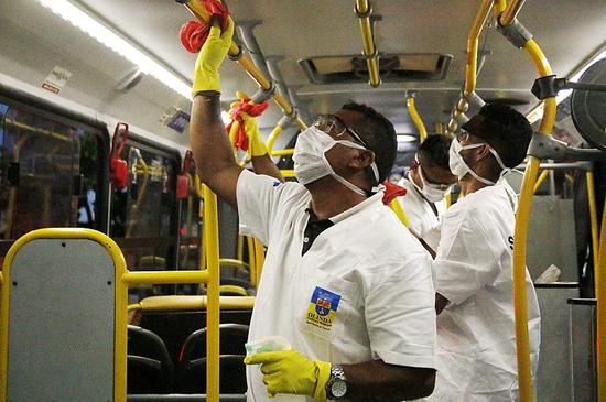 3月16日,巴西伯南布哥州奥林达市,卫生工作人员正在给公交车消毒。/Prefeitura de Olinda