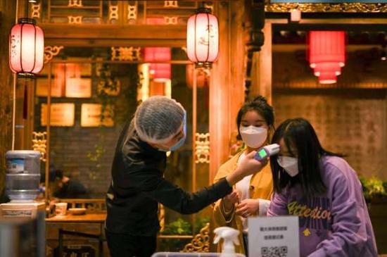 成都一家餐馆门口,服务员检查一名顾客体温。(图源:Getty)