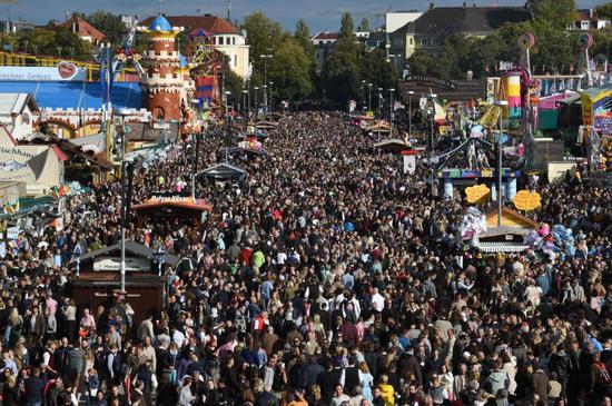 2019年10月3日,在德国慕尼黑,游客参加慕尼黑啤酒节。新华社/法新
