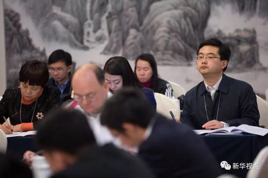 国办工作人员王征宇(右一)在旁听十三届全国人大一次会议广东代表团审议政府工作报告(3月5日摄)。  新华社记者 金立旺 摄