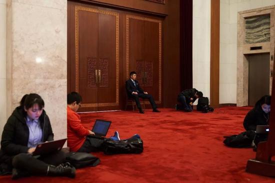 记者们在会议间歇席地而坐,紧张写稿