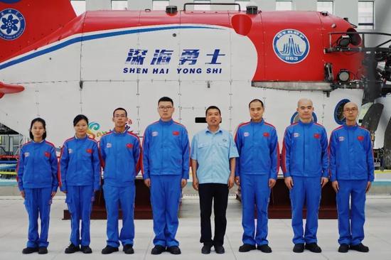 """△深海勇士""""载人潜水器总设计师胡震(右四)与七名潜航员"""