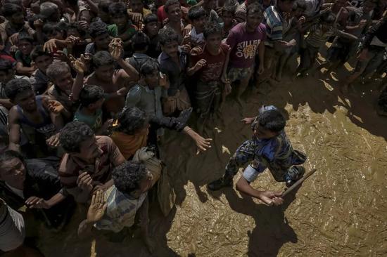 2017年9月21日,一名安全官员试图控制等待接受援助的罗兴亚难民。