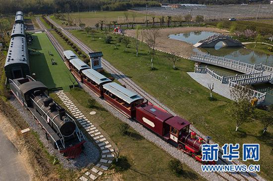 游客乘坐观光小火车从浙江省安吉县鲁家村的休闲驿站边驶过(3月23日无人机拍摄)。新华社记者 黄宗治 摄