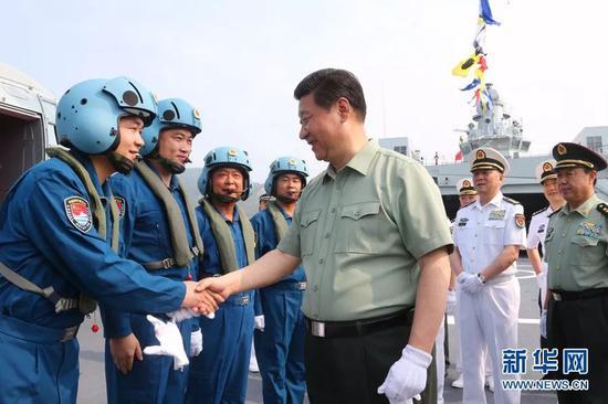 △习近平与舰载直升机飞行员亲切握手。